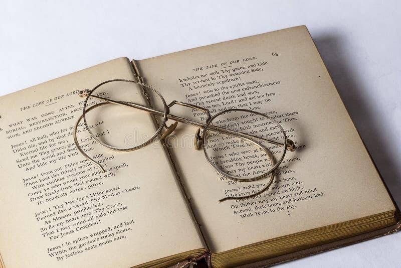 Un paio degli occhiali antichi che si siedono su un innario d'annata aperto su un fondo bianco immagine stock libera da diritti