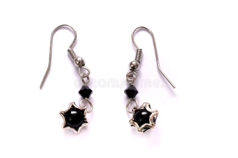 Un paio degli orecchini a forma di stella neri del lobo immagini stock