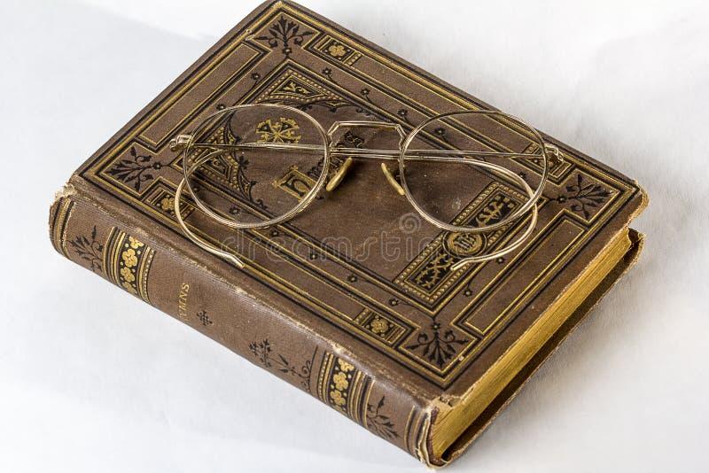 Un paio dei biofocals antichi che si siedono su un innario d'annata su un fondo bianco immagini stock