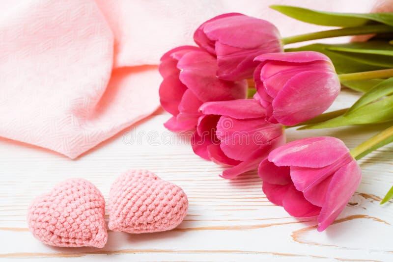 Un paio dei cuori rosa tricottati e di un mazzo dei tulipani freschi su una tavola di legno immagine stock