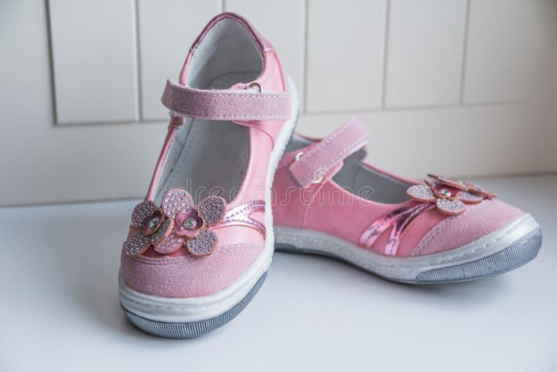 Un paio dei sandali rosa della bambina scarpe di cuoio di rosa di bambino isolate su bianco La bambina copre la raccolta facciata fotografia stock libera da diritti