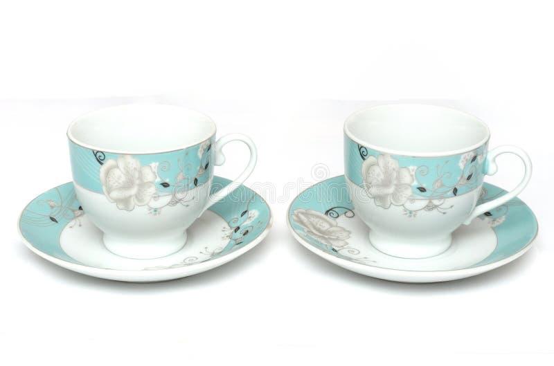 Un paio dei tazza da the di colore chiaro con i piattini fotografie stock libere da diritti
