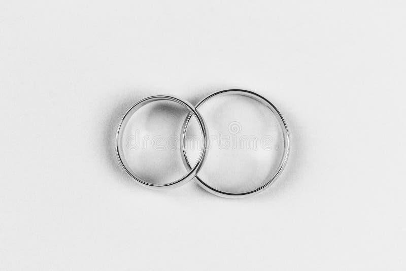 Un paio delle fedi nuziali dell'oro su un fondo bianco, vista superiore fotografia stock libera da diritti