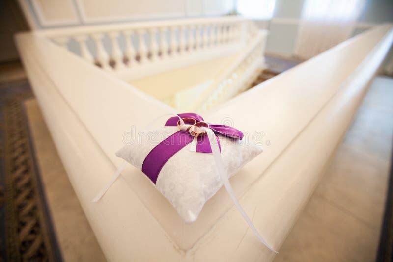 Un paio delle fedi nuziali su un cuscino bianco fotografia stock