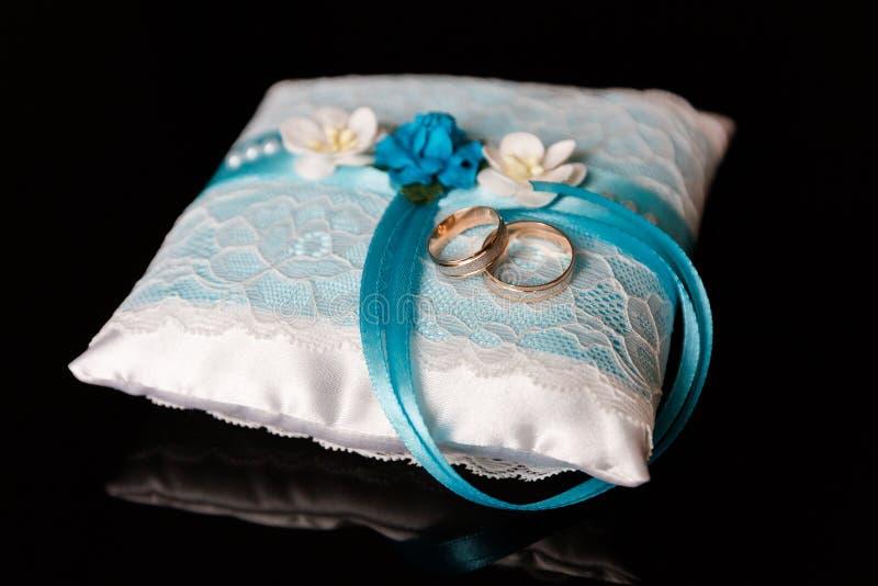 Un paio delle fedi nuziali su un cuscino blu fotografia stock