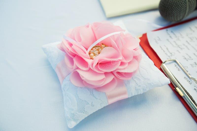 Un paio delle fedi nuziali sul cuscino a forma di del fiore immagini stock libere da diritti