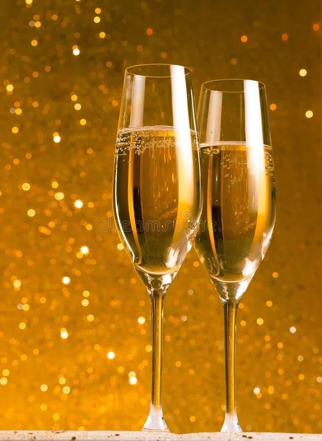Un paio delle flauto di champagne su fondo astratto dorato fotografia stock libera da diritti