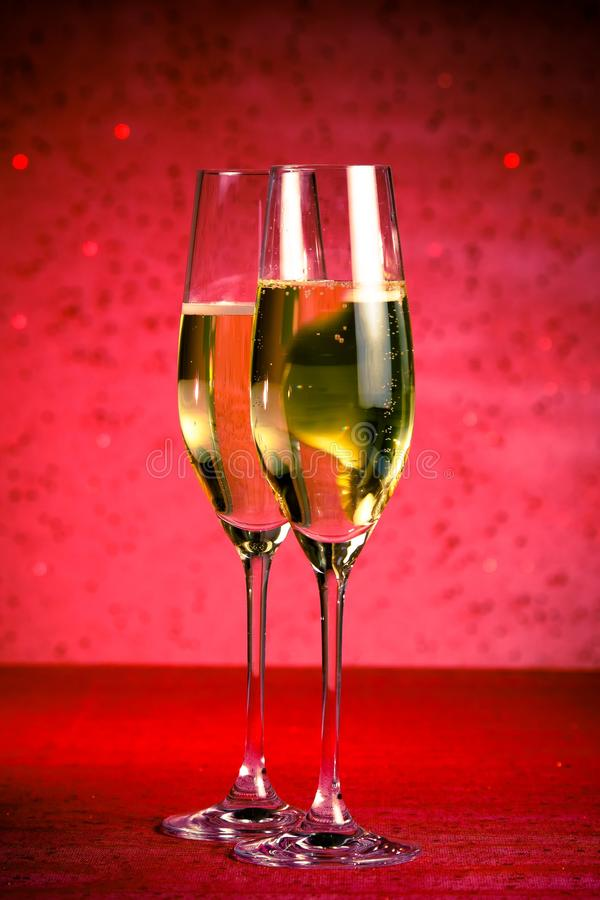 Un paio delle flauto di champagne su fondo astratto rosso fotografie stock libere da diritti