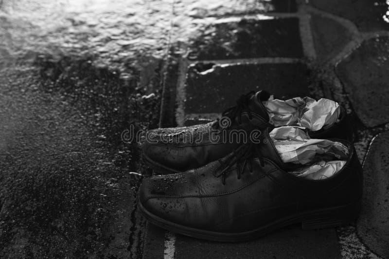 Un paio delle scarpe bagnate in un giorno piovoso fotografie stock