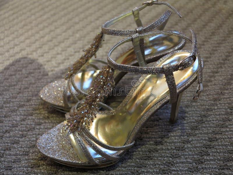 Un paio delle scarpe dei tacchi alti delle signore di progettazione colorate oro bronzeo immagine stock