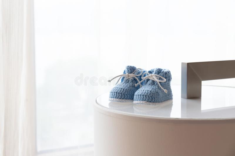 Un paio delle scarpe di bambino blu contro la finestra retroilluminata fotografia stock libera da diritti