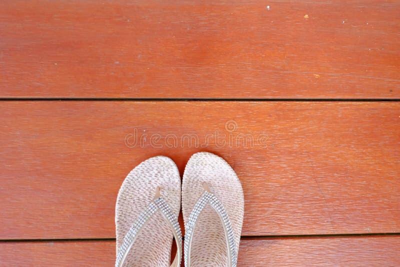 Un paio delle scarpe femminili bianche sul pavimento di legno fotografie stock