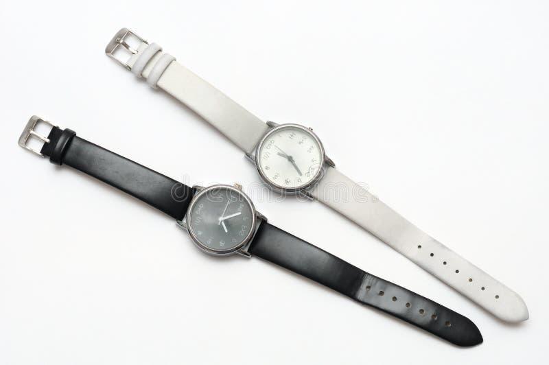 Un paio di contrapposizione in bianco e nero di colore eppure degli orologi simili di progettazione immagini stock libere da diritti