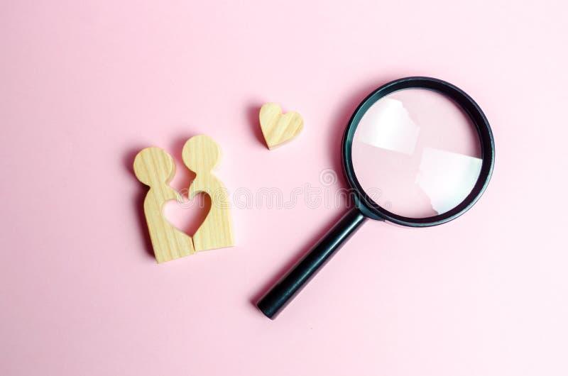 Un paio giovane degli amanti e di una lente d'ingrandimento Ricerca di amore e della creazione di forti relazioni di amore Datazi immagini stock libere da diritti