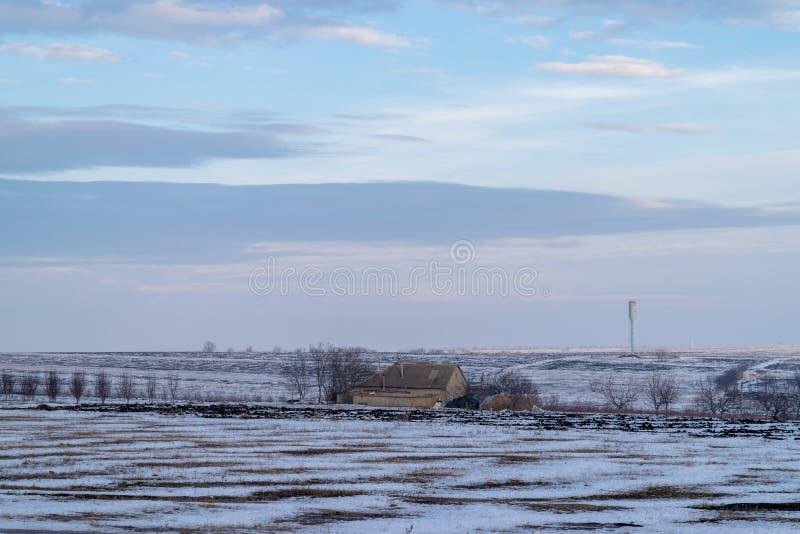 Un paisaje blanco de un terreno con una casa rural en el medio que es cubierto en nieve foto de archivo