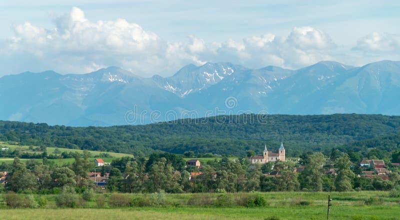 Un paisaje de montañas y de un pueblo con el its& x27; iglesia y casas fotos de archivo libres de regalías