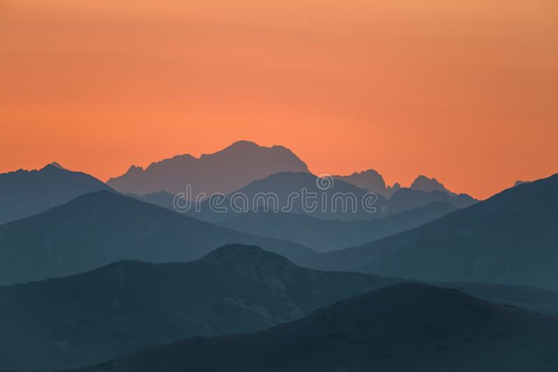 Un paisaje hermoso, colorido, abstracto de la montaña en salida del sol Paisaje minimalista de montañas por mañana en tonos azule fotografía de archivo
