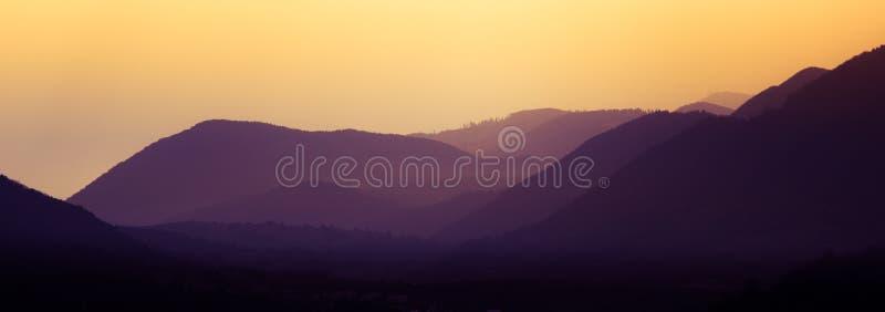Un paisaje hermoso, colorido, abstracto de la montaña en una tonalidad púrpura y anaranjada mística foto de archivo