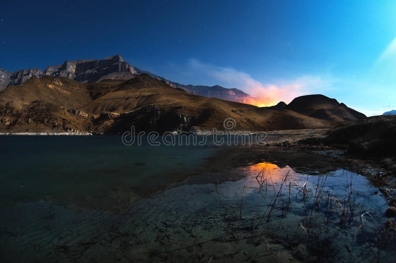 Un paisaje hermoso de la noche con una reflexión de rocas en un lago de la montaña con las montañas ardientes en el fondo foto de archivo