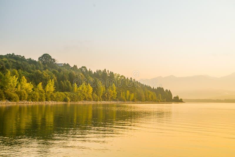 Un paisaje hermoso, tranquilo de la mañana del lago y montañas en la distancia Paisaje colorido del verano con el lago de la mont foto de archivo libre de regalías