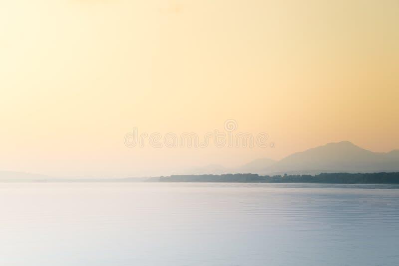 Un paisaje hermoso, tranquilo de la mañana del lago y montañas en la distancia Paisaje colorido del verano con el lago de la mont imagen de archivo libre de regalías