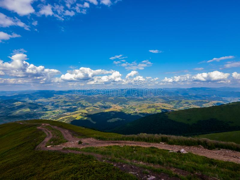 Un paisaje magnífico de montañas y de valles con un camino de tierra que va abajo de una cuesta verde y de nubes bajo flotantes fotos de archivo