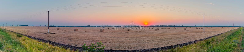 Un pajar en un campo de trigo seco, escaso con las líneas eléctricas contra el contexto del sol poniente y una tarde hermosa foto de archivo libre de regalías