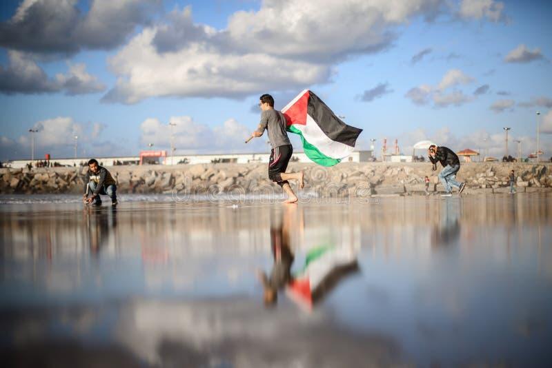 Un Palestinese che porta una bandiera sulla spiaggia fotografia stock libera da diritti