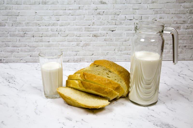 Un pan del pan blanco cortó con un vidrio de la jarra de leche contra un tablero de mármol blanco foto de archivo
