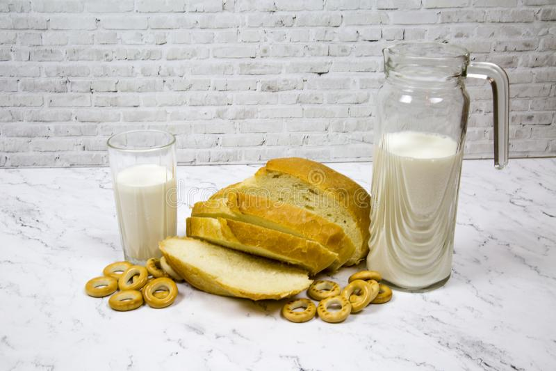 Un pan del pan blanco cortó con un vidrio de la jarra de leche contra un tablero de mármol blanco fotos de archivo