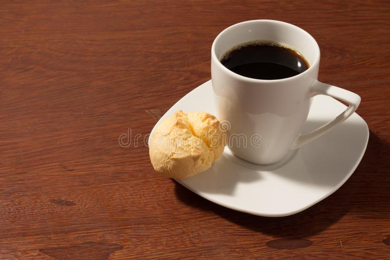 Un pane brasiliano del formaggio con una tazza bianca di caffè nero - con spazio per copy pao de queijo fotografia stock libera da diritti