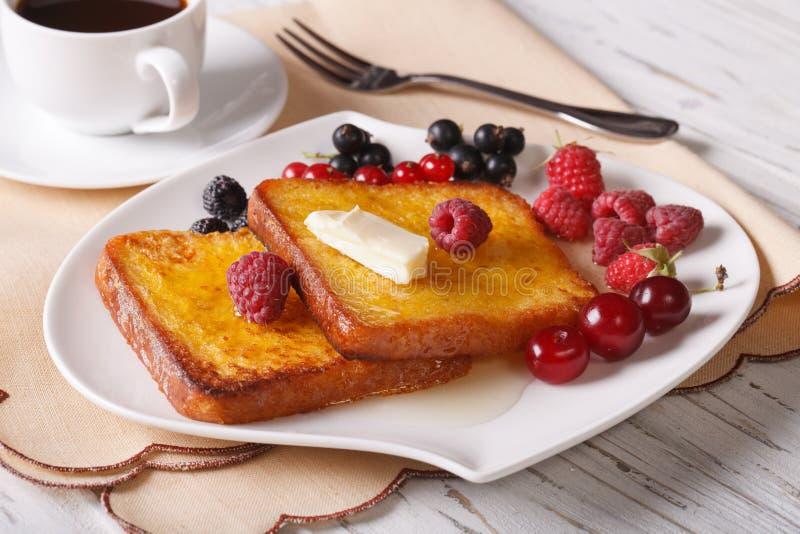 Un pane tostato di due dolci con miele ed il primo piano delle bacche orizzontale fotografia stock libera da diritti