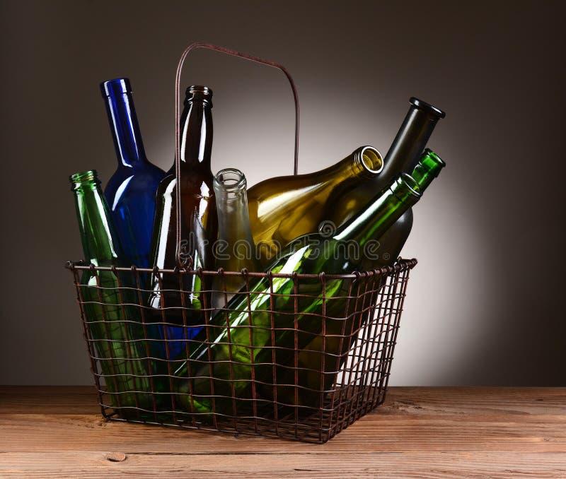 Un panier à provisions de fil rempli de bouteilles vides photographie stock
