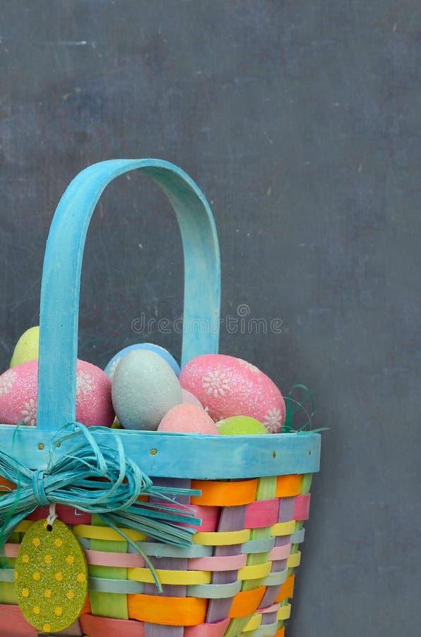 Un panier coloré de Pâques complètement des oeufs scintillants dans bleu, rose, jaune et vert avec l'espace de copie sur un fond  photographie stock libre de droits