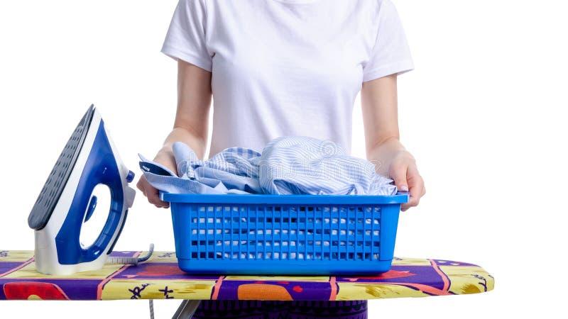 Un panier de blanchisserie chez la main et le fer de la femme sur la planche à repasser photo stock