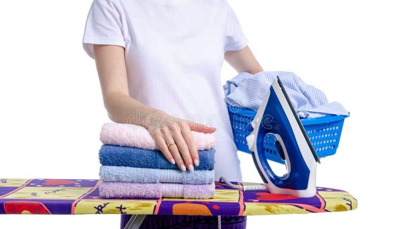 Un panier de blanchisserie chez la main et le fer de la femme sur la planche à repasser photos stock