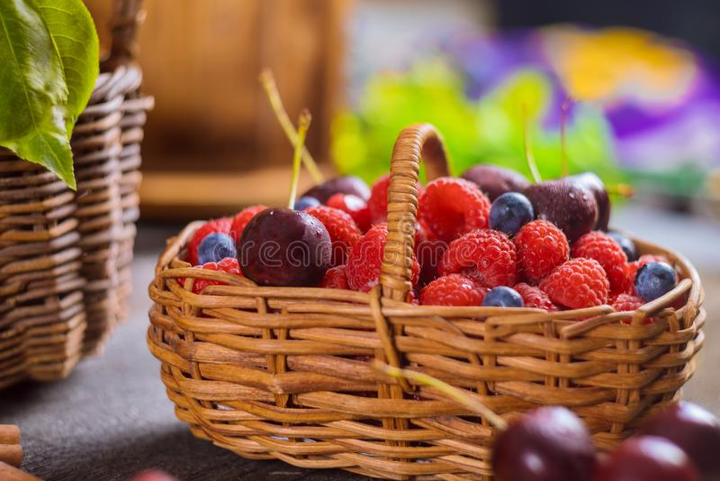 Un panier des baies mélangées myrtille, cerise, foyer sélectif d'été de nourriture saine de framboise photographie stock
