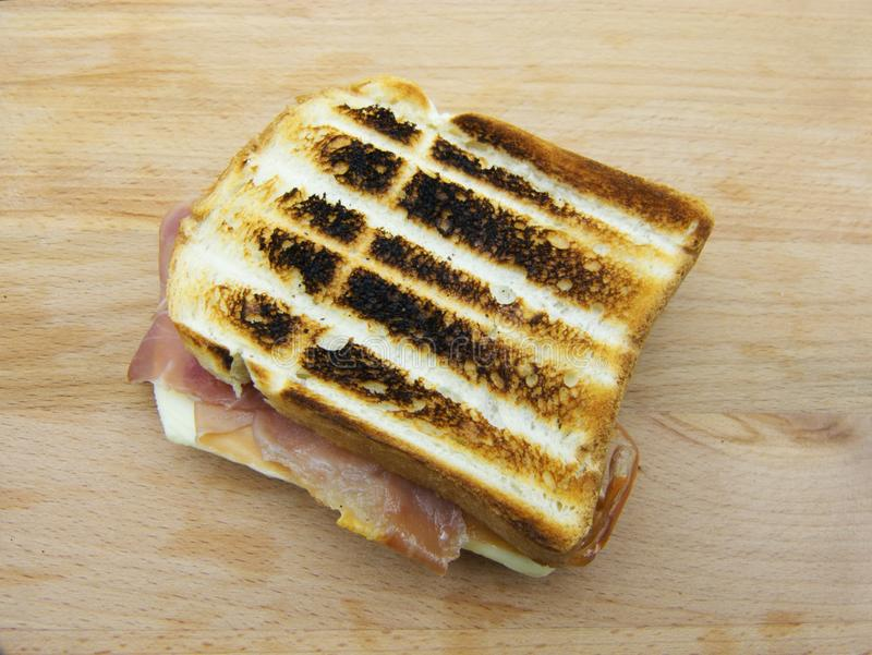 Un panino arrostito del formaggio e del prosciutto su fondo di legno fotografie stock libere da diritti