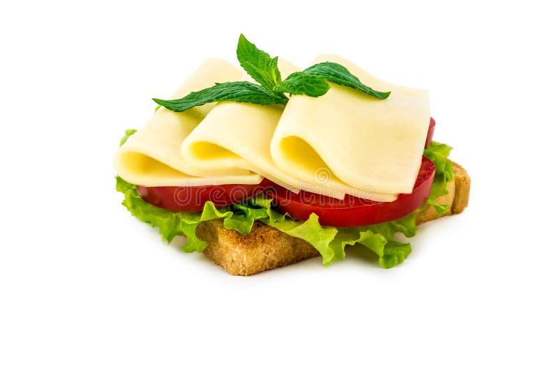 Un panino con formaggio, pomodoro, insalata, su un fondo isolato bianco immagine stock