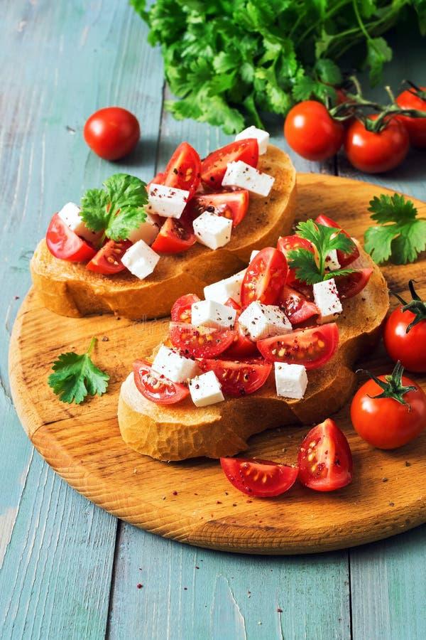 Un panino con i pomodori ed il formaggio Bruschetta tradizionale italiana con i pomodori su una tavola verde rustica Fuoco selett immagini stock libere da diritti