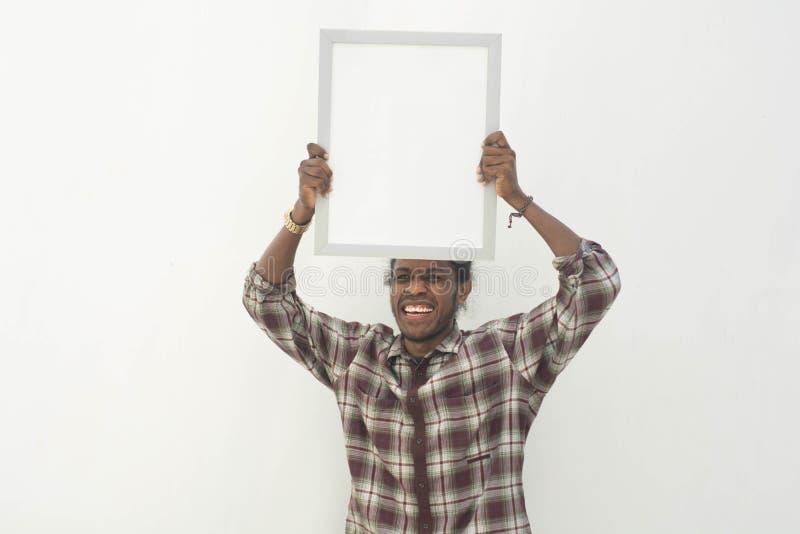 Un panneau blanc du jeune d'homme de couleur de participation espace de copie avec le fond d'isolement dans le blanc photographie stock