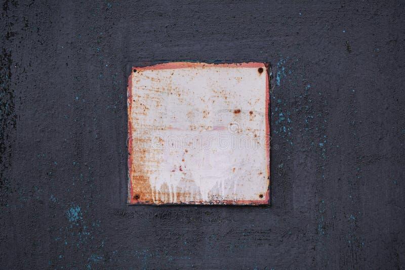 Un panneau carré en aluminium avec un cadre rouge sur un vieux mur noir en métal peint photo stock