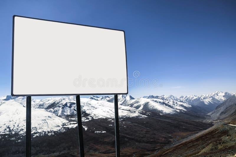 Un panneau d'affichage vide blanc extérieur avec vue sur le ciel bleu et la neige clairs a couvert la gamme de montagne à l'arriè images libres de droits