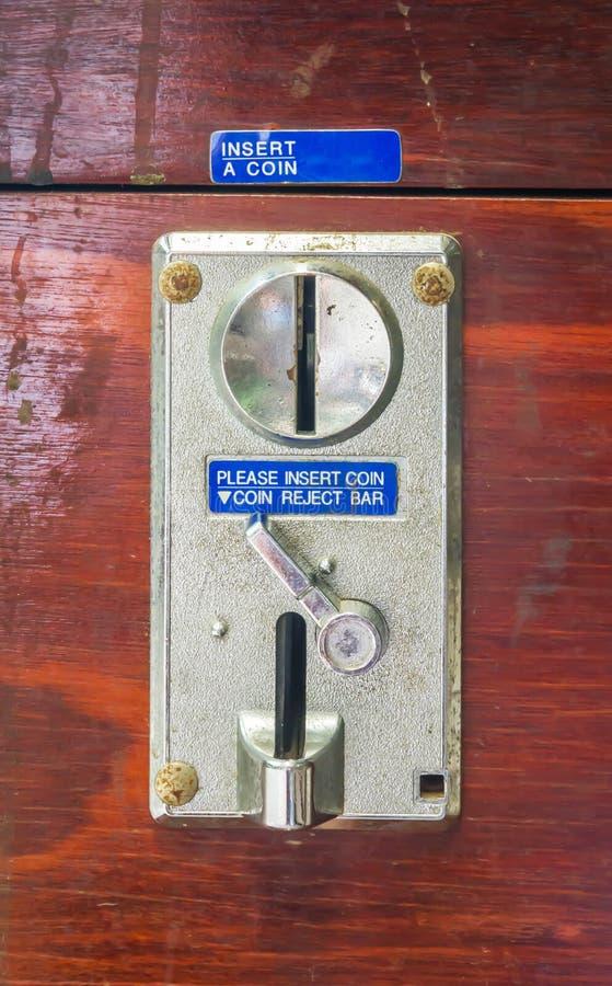 Un panneau de fente de pièce de monnaie en métal d'une machine à jetons photos stock