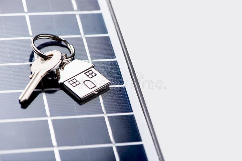 Un pannello solare con la chiave della casa fotografie stock libere da diritti