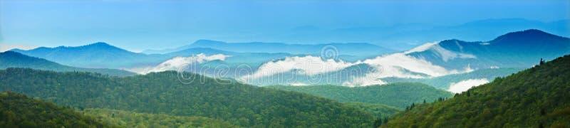 un panorama di 180 gradi di grandi montagne fumose fotografia stock