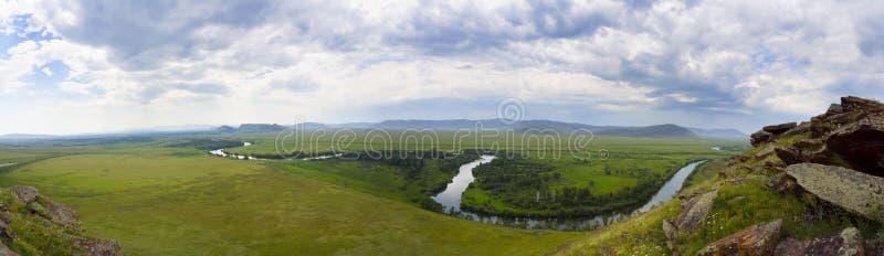 Un panorama grande de un prado verde hermoso con las montañas en el fondo y un río a lo largo de su toda la longitud imagen de archivo
