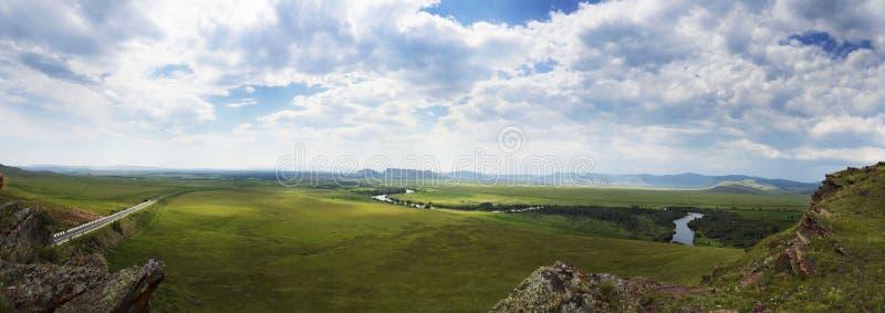 Un panorama magnifique des champs verts d'une colline Vous pouvez voir la route et les montagnes Rivière à travers le paysage photos libres de droits