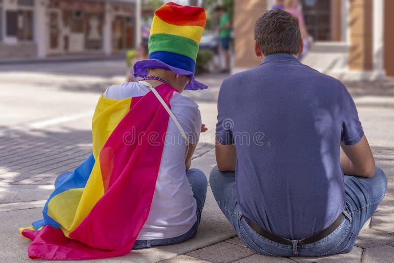 Un papá de apoyo se sienta con su hija en Pride Fest imagenes de archivo