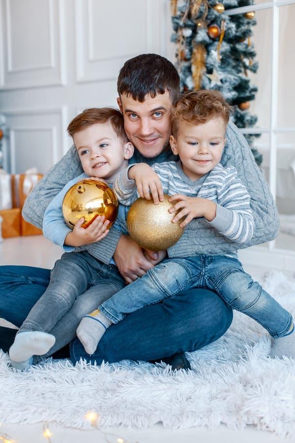 Un papá de a con sus gemelos de dos hijos delante del árbol de navidad que abraza y que se divierte Concepto de familia grande foto de archivo